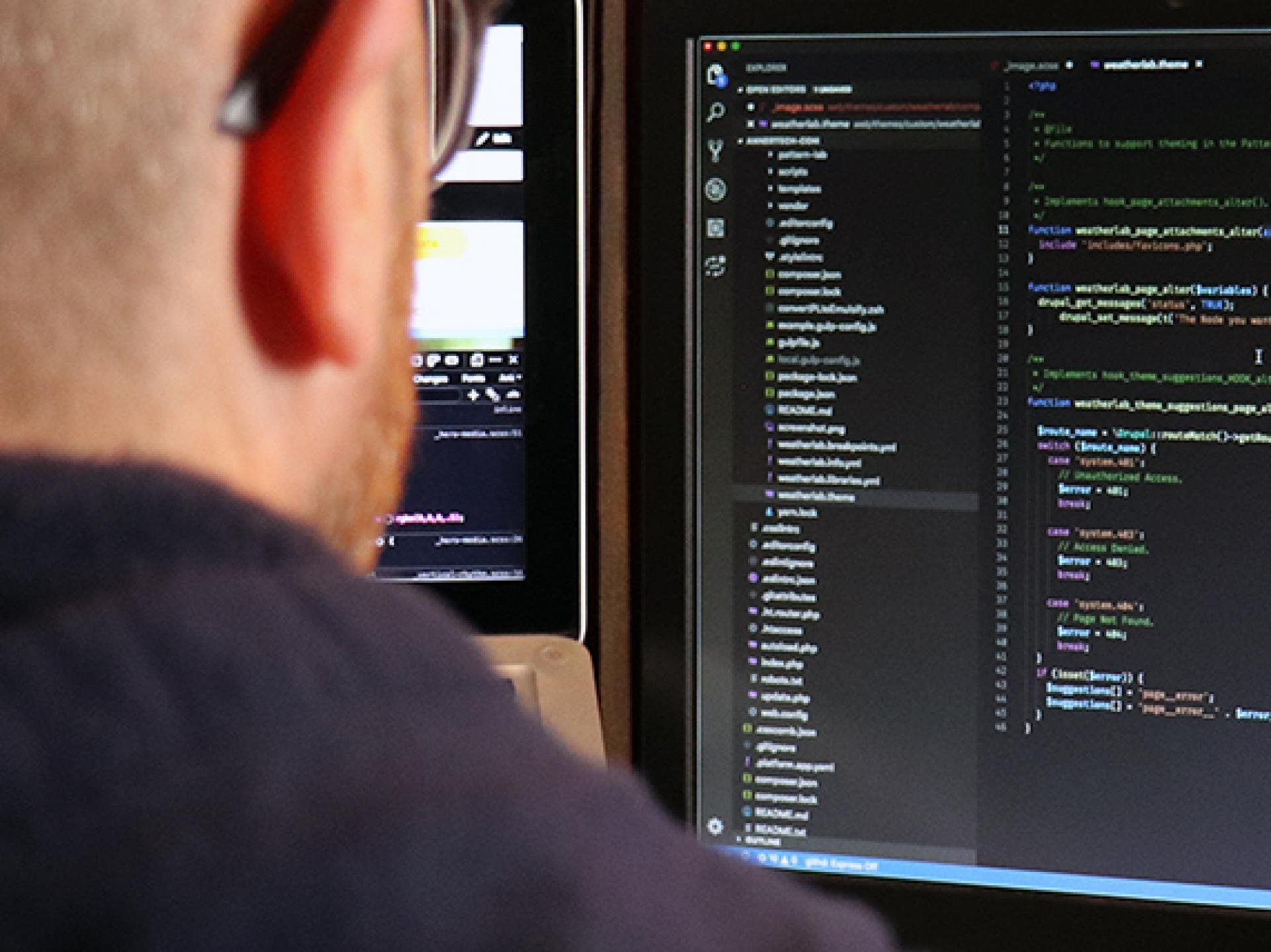 Man sitting at computer with code on the screen | Annertech Development Services